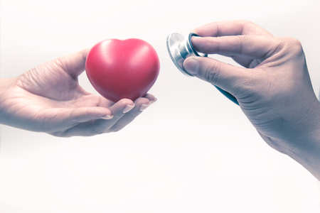 Man holding stethoscope and checking heart in woman hand; health care concept on white background Stockfoto