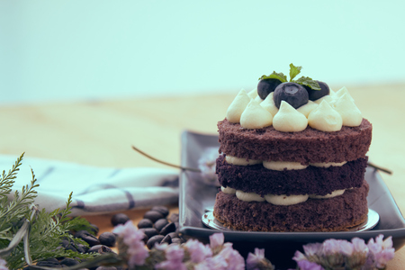 Brown cake with berry on top placing with pink flower as decorated item on the wooden table 写真素材