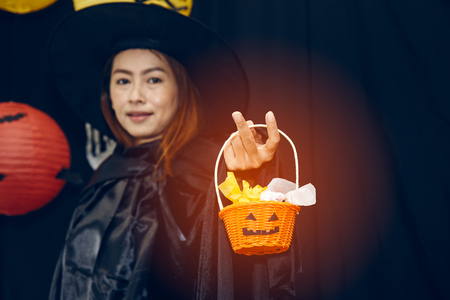 Halloween Concept; Beautiful Witch toss the candy in pumpkin basket on black background