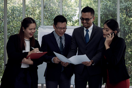 Teamwork concept; four businessman and woman standing and check drawing together in meeting room with smiling and happiness