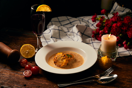 Delicious Roasted corn with cream sauce placing on white dish together with catering, lemon and wine in dark light background by candle light