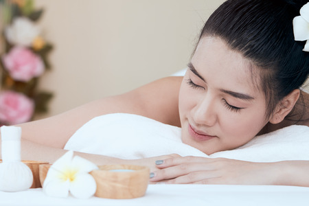 Close up of attractive young Asian woman smiling and getting Spa treatment on white bed