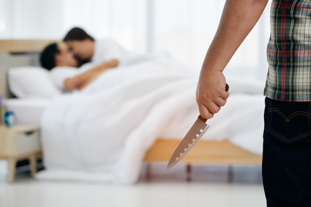 Husband holding knife before killing wife and adulterer in bed room Standard-Bild