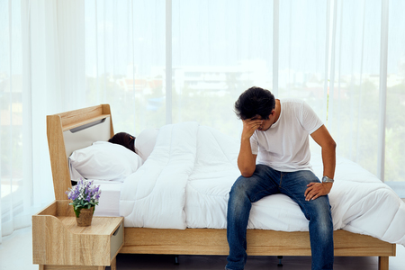 husband sitting and depress on bed while wife sleep without response anything