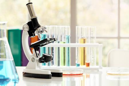 Microscopio de mesa con equipo de laboratorio en laboratorio químico con destello de luz; Concepto de investigación y desarrollo de laboratorio de ciencia