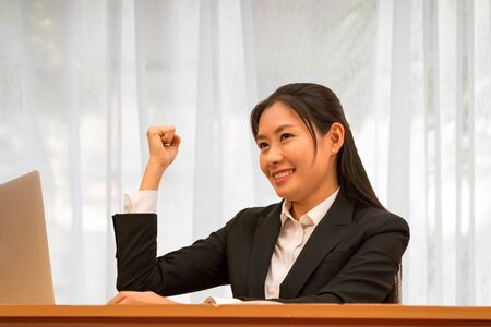 Asian woman successing and smile with arm up on white curtain background