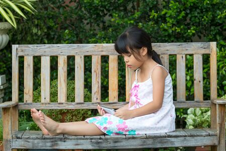 Cute Asian Girl sitting on wooden chair in park and watching cartoon in mobile phone which using internet for on-line channel