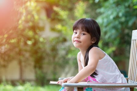 Cute Asian girl looking outside while sitting and reading book in Park