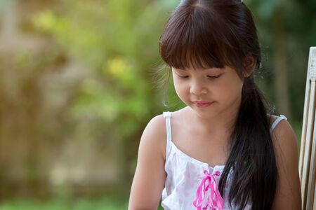 Cute Asian girl looking down while sitting in public Park Banco de Imagens