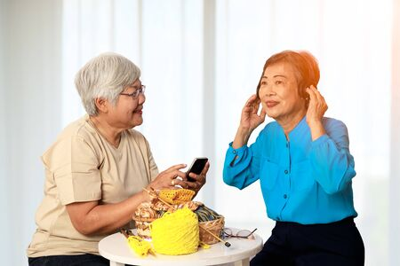 Two Asian 70s seniors enjoy activity together in living room with white curtain, listening online music from mobile phone while doing knitting