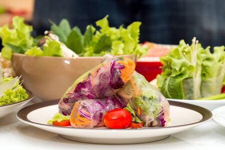 Close up of Fresh spring roll on disk placing together with other fresh vegetable