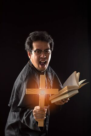 Dark tone, rim light - Priest show crucifix while holding bible to exorcise ghost on black background