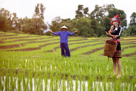 Female Asian Hmong holding mobile phone and wonder feeling while male farmer suspending Stock Photo