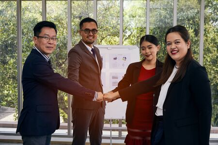Teamwork concept; businessman and woman standing and punch hands together in meeting room before starting competition work