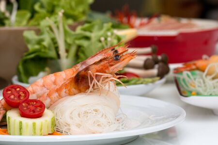 Close up of delicious shrimp on rice noodles in white disk placing together with various ingredient as background Stockfoto