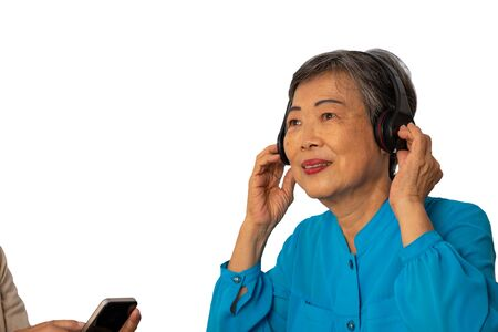 Portrait of two Asian seniors listening to music by wireless headphone and mobile phone on white background with clipping path Banco de Imagens