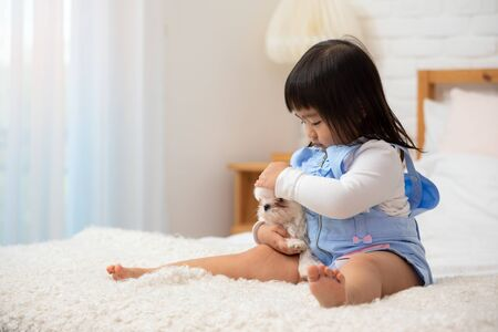 Asian 3-years child sitting on white bed and hug little white Maltese dog with care and tender