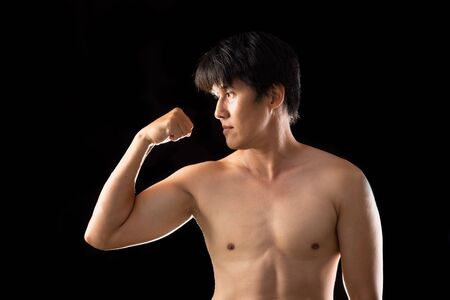 Muscle Boxer Shaped Asian Man raising right hand posting side view on black background Banco de Imagens