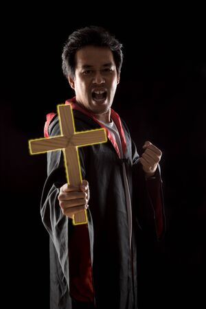 Dark tone, rim light - Priest show lighting crucifix while holding bible to exorcise ghost on black background
