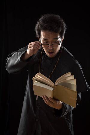 Young Priest catch glasses and panic while looking at old Bible on black background