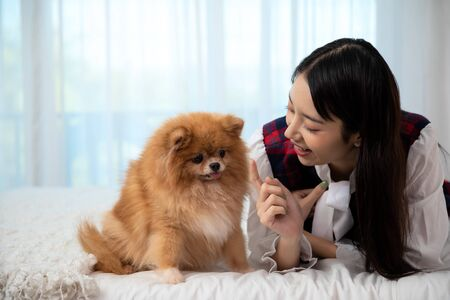 Young pretty Asian woman lying and teasing hand to Brown Pommeranian dog on white bed