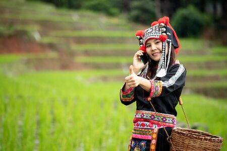 Portrait of Asia hmong lady calling by mobile phone and thumb up while walking in rice field