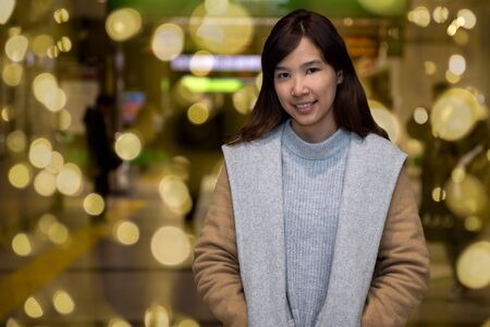 Woman in city at night; Portrait of young woman in brown sweater on background of station with golden bokeh