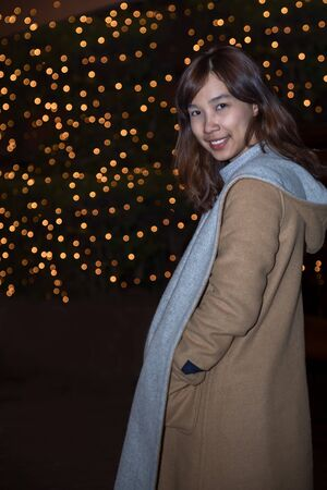 Woman in city at night; Portrait of young woman in brown sweater on background bokeh light in night atmospheric city Banco de Imagens