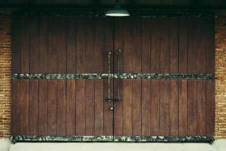 Old warehouse as dark brwon wooden sliding door with brown brick wall and lamp