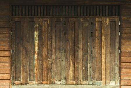 Old brown vintage window on wooden wall of Residential, home acient design. Banco de Imagens