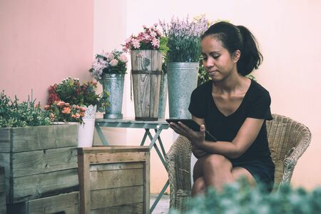 Asian Female owner of plant shop sitting next to a selection of plants on wooden box, holding digital tablet.