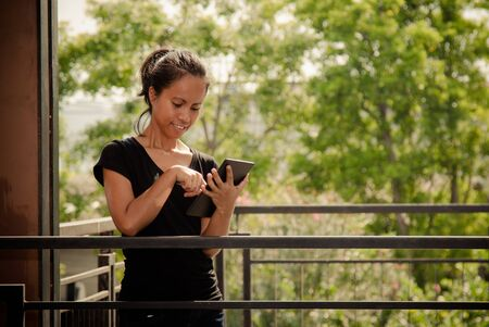 Young Asia woman in black T shirt smiling and playing tablet at terrace with copy space Banco de Imagens