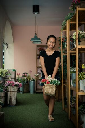 Asia female  owner holding basket with pink and white rose in  flower store