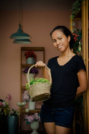 Asia female owner holding basket with yellow and green flower in store