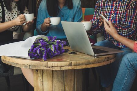 Four women do meeting by sharing information from notebook and drinking coffee in coffee shop with warm light flare tone