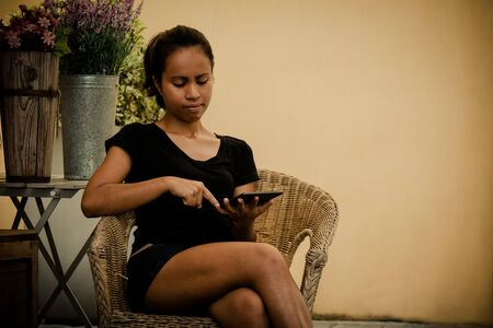 Asian Female owner of plant shop sitting next to a selection of plants on wooden box, holding digital tablet