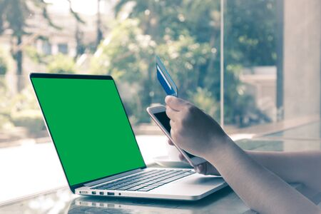 Male customer order goods from internet shopping and pay by credit card; Laptop with green screen