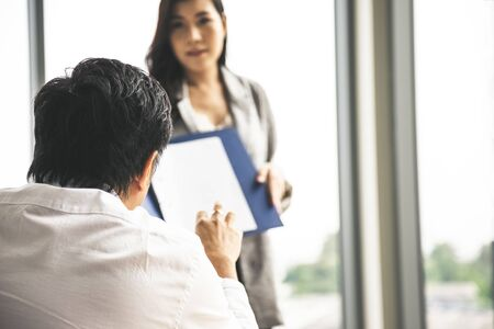 Asian manager rise hand to ask question during sale woman present summary report in meeting room