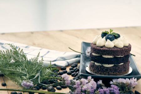 Brown cake with berry on top placing with pink flower as decorated item on the wooden table Banco de Imagens