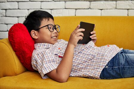 Asian boy smiling playing with tablet wihle laying on yellow sofa