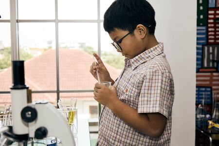 Close up of Little Asian boy with glassess hold beaker in the laboratory Banco de Imagens