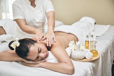 Young Asian beautiful women lying down on bed and getting oil massaging from therapist in Spa Treatment Salon