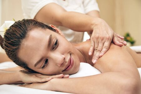Young Asian beautiful woman lying down on bed and getting oil massaging treatment by therapist