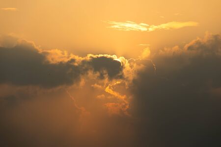Close up of Sun rise in orange sky during cloudy in early morning; dawn and bright time
