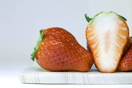 Close up of Red strawberries full and half placing on a wooden plate Banco de Imagens