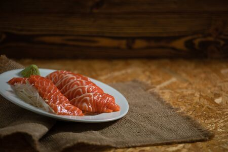 Sliced salmon placing on dish together wasabi and radish on wooden plate with copy space 版權商用圖片 - 148094446