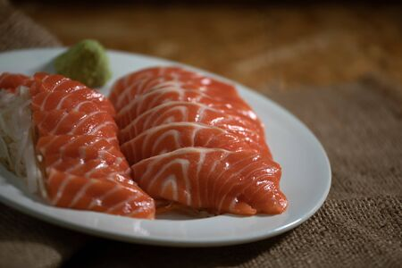 Close up of Sliced salmon placing on dish together wasabi and radish on wooden plate with copy space 版權商用圖片