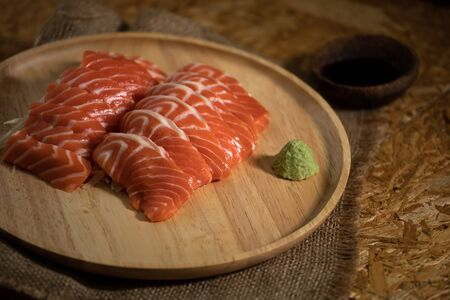 Close up of Sliced salmon placing on wooden plate together wasabi radish and shoyu on burlap table Imagens