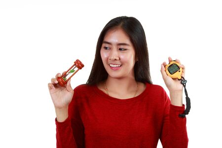 Young Asian lady checking Timer by hourglass or stop watch on white background; holding retro clock and digital clock