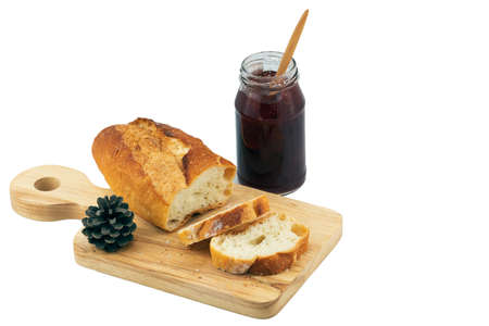 Fresh Homemade Sliced French Baguette Bread on wooden plate with jam bottle on white background